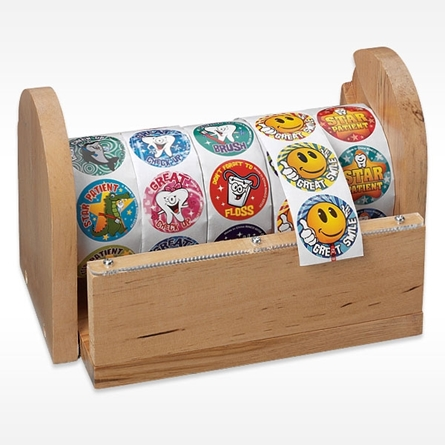 5 Rolls of Dental Themed Stickers  on a solid wood dispenser with safe plastic cutting edge can be mounted on a wall or placed on a desk